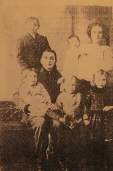 Seated: Harry E. Goudy, Sr., holding Harry E., Jr.; Standing Front: Helen and Carrie; Standing Back: Clarence (Keg) and Mother Mabel holding Russel